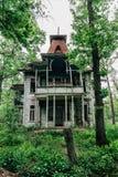 Παλαιό όμορφο εγκαταλειμμένο ξύλινο σπίτι μεταξύ των δέντρων και της πράσινης χλόης Στοκ εικόνα με δικαίωμα ελεύθερης χρήσης