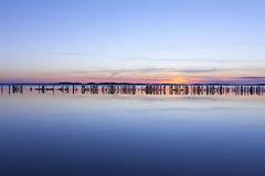 Παλαιό groyne στη λιμνοθάλασσα στο ηλιοβασίλεμα Στοκ Εικόνα