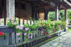 Παλαιό patio σπιτιών με τα λουλούδια στον ξύλινο φράκτη Στοκ φωτογραφία με δικαίωμα ελεύθερης χρήσης