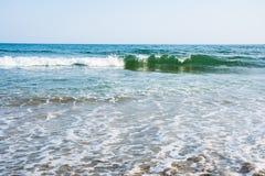 Παλιρροιακά κύματα θάλασσας με τον άσπρο αφρό σε μια ηλιόλουστη αμμώδη παραλία στο θέρετρο Στοκ εικόνες με δικαίωμα ελεύθερης χρήσης