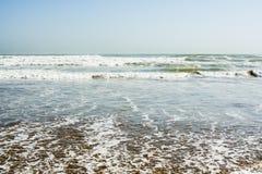 Παλιρροιακά κύματα θάλασσας με τον άσπρο αφρό σε μια ηλιόλουστη αμμώδη παραλία στο θέρετρο Στοκ Φωτογραφίες