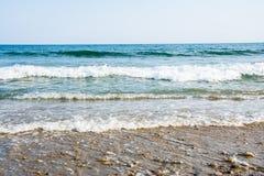 Παλιρροιακά κύματα θάλασσας με τον άσπρο αφρό σε μια ηλιόλουστη αμμώδη παραλία στο θέρετρο Στοκ Φωτογραφία