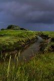 Παλιρροιακός κολπίσκος με το θυελλώδη ουρανό στοκ εικόνα με δικαίωμα ελεύθερης χρήσης