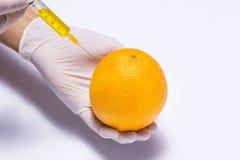 Πείραμα επιστήμης το πορτοκάλι και τη σύριγγα που απομονώνονται με στο λευκό Στοκ Εικόνες