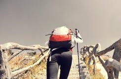 Πεζοπορία γυναίκα που αναρριχείται μέχρι την αιχμή βουνών Στοκ Φωτογραφία