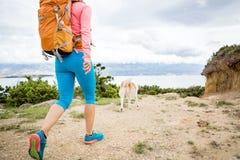 Πεζοπορία γυναικών που περπατά με το σκυλί στο ίχνος παραλιών Στοκ φωτογραφία με δικαίωμα ελεύθερης χρήσης