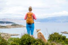Πεζοπορία γυναικών που περπατά με το σκυλί στο ίχνος παραλιών Στοκ Φωτογραφίες