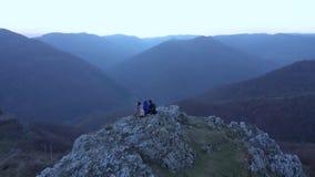 Πεζοπορία ομάδα φίλων που χαλαρώνουν σε έναν απότομο βράχο βουνών Εναέριος κινηματογράφος κηφήνων 4k φιλμ μικρού μήκους