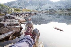 πεζοπορία Πόδια γυναικών με τις μπότες και την άποψη λιμνών βουνών Στοκ Φωτογραφίες