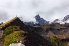 Πεζοπορία στα βουνά που περιβάλλονται από τα σύννεφα στοκ φωτογραφία