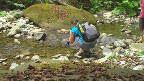 Πεζοπορία όμορφη γυναίκα με το σακίδιο πλάτης που κάθεται οκλαδόν και που κάνει τη φωτογραφία από το smartphone στον ποταμό βουνώ απόθεμα βίντεο