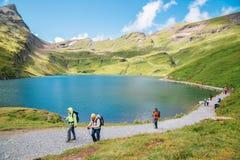 Πεζοποριεις άνθρωποι και λίμνη Bachalpsee στο ελβετικό βουνό Grindelwald Άλπεων πρώτα σε Grindelwald, Ελβετία στοκ εικόνες