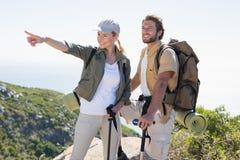 Πεζοποριες ζεύγος που δείχνει και που εξετάζει την κορυφή βουνών Στοκ Φωτογραφία