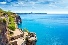 Πεζούλι στον απότομο βράχο κοντά στον μπλε Κόλπο Antalya στη δημοφιλή παραλία σχετικά με Στοκ Εικόνες