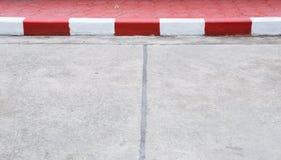 Πεζοδρόμιο με την κόκκινη και άσπρη συγκράτηση Στοκ Φωτογραφίες