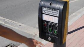 Πεζός που πιέζει το κουμπί αναμονής προκειμένου να διασχιστεί η οδός ακίνδυνα Οδική ασφάλεια απόθεμα βίντεο