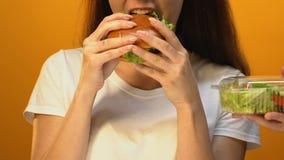 Πεινασμένη γυναίκα που επιλέγει το λιπαρό χάμπουργκερ αντί της πράσινης σαλάτας, κίνδυνος υπερβολικού βάρους απόθεμα βίντεο