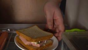 Πεινασμένος άγαμος που λαμβάνει το ψυγείο σάντουιτς κοντά, κακή ποιότητα ζωής, καταναλωτισμός απόθεμα βίντεο