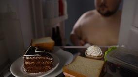 Πεινασμένος άγαμος που παίρνει το κέικ κρέμας από το ψυγείο, νόστιμο επιδόρπιο, γρήγορο φαγητό τη νύχτα φιλμ μικρού μήκους