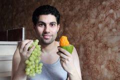 Πεινασμένος αραβικός νεαρός άνδρας με τα φρούτα και το σταφύλι μάγκο Στοκ Φωτογραφία