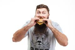 Πεινασμένος γενειοφόρος νεαρός άνδρας που τρώει το χάμπουργκερ Στοκ Εικόνες