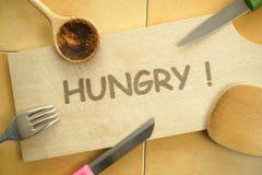 Πεινασμένος! κείμενο στον τέμνοντα πίνακα άλλα μαχαιροπήρουνα γύρω Στοκ Εικόνες