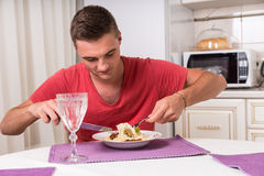 Πεινασμένος νεαρός άνδρας που τρώει τα ζυμαρικά να δειπνήσει στον πίνακα Στοκ Εικόνες