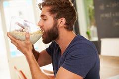 Πεινασμένος νεαρός άνδρας που τρώει το πρόγευμα από το κύπελλο γυαλιού Στοκ εικόνες με δικαίωμα ελεύθερης χρήσης