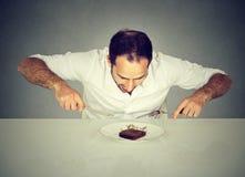Πεινασμένο άτομο που ποθεί το γλυκό κέικ λιβρών τροφίμων Στοκ φωτογραφία με δικαίωμα ελεύθερης χρήσης