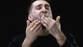 Πεινασμένο αρσενικό που τρώει λαίμαργα το κέικ στο σκοτεινό κλίμα, πρόβλημα βουλιμίας απόθεμα βίντεο
