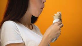 Πεινασμένο κορίτσι που τρώει το shawarma, που απολαμβάνει τα εύγευστα αλλά ανθυγειινά τρόφιμα, εθισμός φιλμ μικρού μήκους