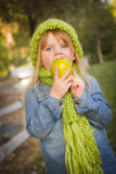 Πεινασμένο κορίτσι που φορούν το πράσινο μαντίλι και καπέλο που τρώει τη Apple έξω Στοκ Εικόνες