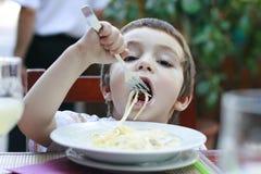 Πεινασμένο μικρό παιδί που τρώει τα μακαρόνια στοκ εικόνες