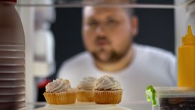 Πεινασμένο παχύ άτομο που εξετάζει τα κέικ κρέμας στο ψυγείο τη νύχτα, κίνδυνος διαβήτη, ζάχαρη στοκ φωτογραφίες