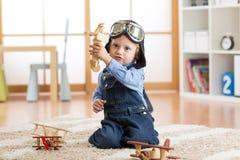 Πειραματικά παιδικά παιχνίδια αεροπόρων με τα ξύλινα αεροπλάνα παιχνιδιών στο πάτωμα στο δωμάτιό του Στοκ Εικόνα