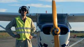 Πειραματικός στις ομοιόμορφες στάσεις κοντά σε ένα αεροπλάνο Ο αρσενικός αεροπόρος εξετάζει μια κάμερα, που φορά το ειδικό σύνολο απόθεμα βίντεο
