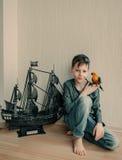 Πειρατής αγοριών με έναν παπαγάλο και sailboat Στοκ Εικόνες