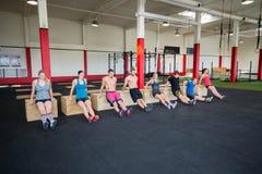 Πελάτες που εκτελούν τις εμβυθίσεις Triceps στη γυμναστική στοκ φωτογραφίες