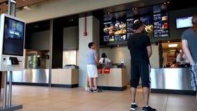 Πελάτες που περιμένουν τις διαταγές τροφίμων σε McDonald ` s Πανεπιστήμιο χάμπουργκερ απόθεμα βίντεο