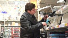 Πελάτης ατόμων στο κατάστημα που φαίνεται επιτραπέζιος λαμπτήρας Επιλογή ενός λαμπτήρα ανάγνωσης για την οικογένεια φιλμ μικρού μήκους