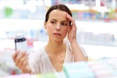 Πελάτης με τον πονοκέφαλο που επιλέγει τα φάρμακα στο φαρμακείο στοκ φωτογραφία