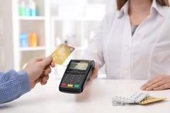 Πελάτης που χρησιμοποιεί την πιστωτική κάρτα για την τελική πληρωμή στο φαρμακείο στοκ εικόνα με δικαίωμα ελεύθερης χρήσης