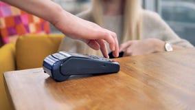 Πελάτης στον καφέ που κάνει τη σε απευθείας σύνδεση πληρωμή που χρησιμοποιεί το smartphone 4K φιλμ μικρού μήκους