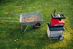 Πελέκι κήπων, ηλεκτρικός καταστροφέας εγγράφων mulcher με wheelbarrow το σύνολο της ξύλινης προστασίας στοκ εικόνες