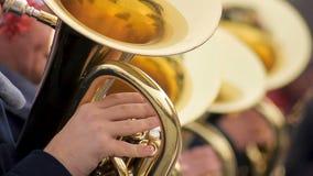 Πεπειραμένα άτομα από την ορχήστρα πνευστ0ών από χαλκό που παίζει επιμελώς στους σωλήνες, εορταστική διάθεση φιλμ μικρού μήκους
