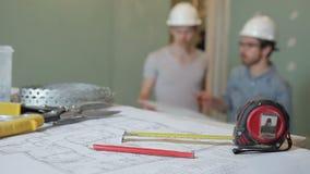 Πεπειραμένοι οικοδόμοι που συζητούν την επισκευή σχεδίων που στέκεται στο εσωτερικό Κρατούν στο πρόγραμμα χεριών της λήξης των ερ απόθεμα βίντεο