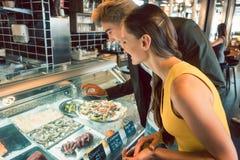 Πεπειραμένος αρχιμάγειρας που επιλέγει τα ακατέργαστα θαλασσινά από τον ψυκτήρα για δύο πελάτες στοκ εικόνα