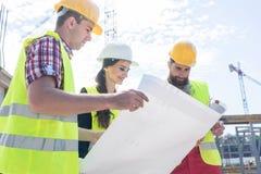 Πεπειραμένος αρχιτέκτονας που αναλύει ένα σχεδιάγραμμα στο εργοτάξιο οικοδομής στοκ φωτογραφίες με δικαίωμα ελεύθερης χρήσης