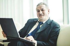 Πεπειραμένος επιχειρηματίας που εργάζεται στη συνεδρίαση lap-top στον καναπέ σε ένα ιδιαίτερο γραφείο Στοκ φωτογραφία με δικαίωμα ελεύθερης χρήσης