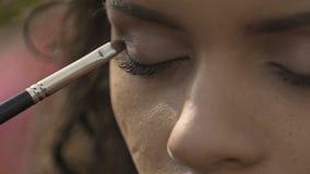 Πεπειραμένος καλλιτέχνης makeup που εφαρμόζει τη σκιά ματιών, που προετοιμάζει το πρότυπο για τη επίδειξη μόδας απόθεμα βίντεο